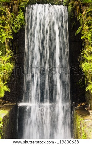 Water Cascade Falls From A High Wall - stock photo