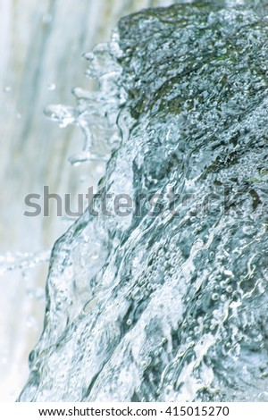 Water cascade waterfall streaming splashes background, large detailed vertical closeup, bright blue, sea green pastel colors, motion blurred drops texture pattern, gentle textured bokeh