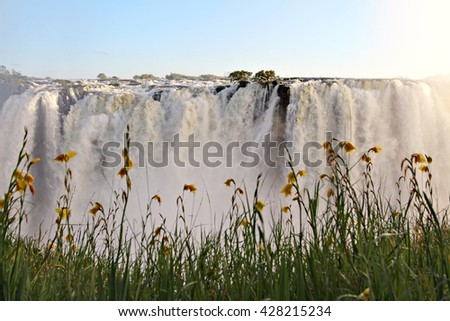 Water cascades over Victoria Falls, one of the Seven Natural Wonders of the World in Zambia, Africa. - stock photo