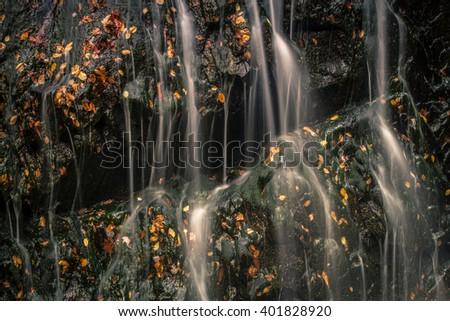 Water cascading over rock with moss and fall leaves. - stock photo