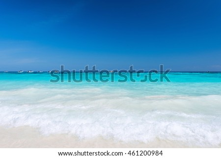 Water clear at the sandy beach with blue sky