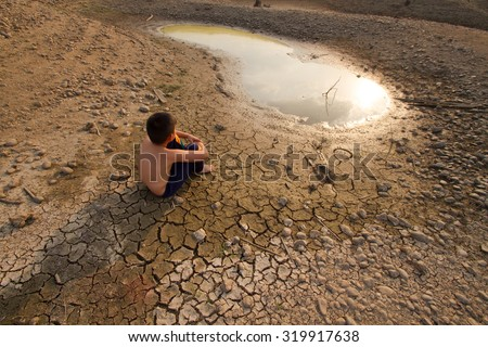 Water crisis, Child sit on cracked earth near drying water. - stock photo