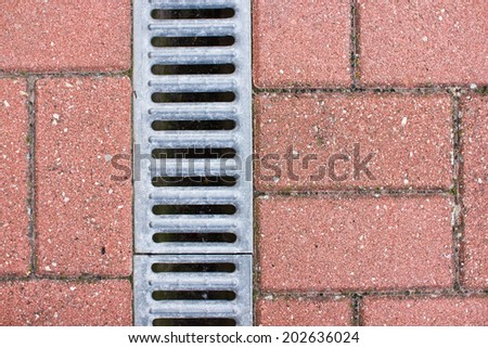 Water drain, metal part and red pavement texture. - stock photo