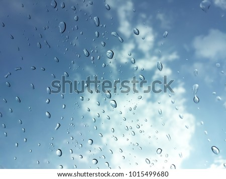 Water drop background on glass of rain abstract bright blue aqua clean bubble with sky cloud closeup nature at rainy day transparent splash droplet texture shower steam on window