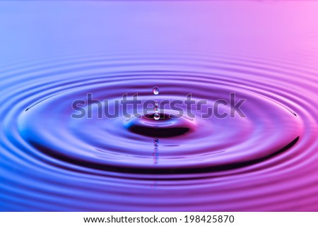 Water drop close up with concentric ripples on colourful blue and pink surface - stock photo