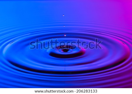 Water drop close up with concentric ripples on colourful blue and pink surface