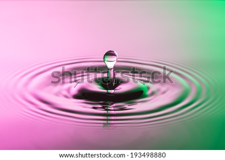 Water drop close up with concentric ripples on colourful pink and green surface - stock photo