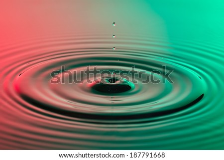Water drop close up with concentric ripples on colourful red and green surface
