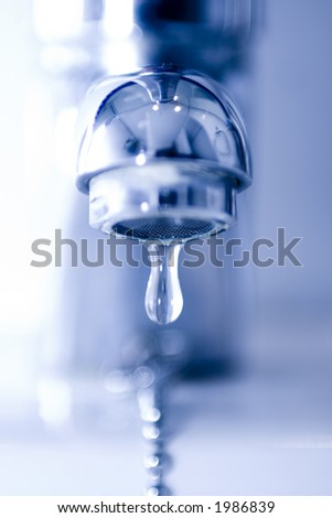 Water drop falling form a faucet in a blue bathroom, low DOF - stock photo