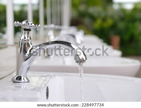 Water drop from faucet on nature background.