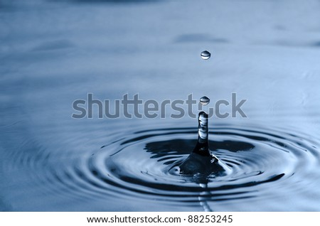 Water drop hitting the clean calm surface of the water - stock photo