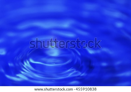Water drop impact on water surface background - stock photo