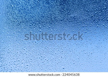 Water drop on a glass made with pastel tones - stock photo