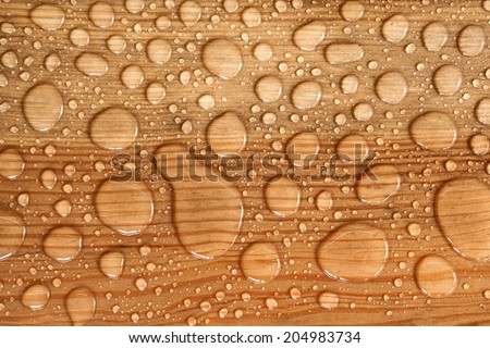 water drop on a wooden background - stock photo