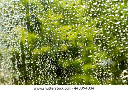 Water drop on glass mirror abstract background.Green Background. Shallow depth of field and selective focus. - stock photo