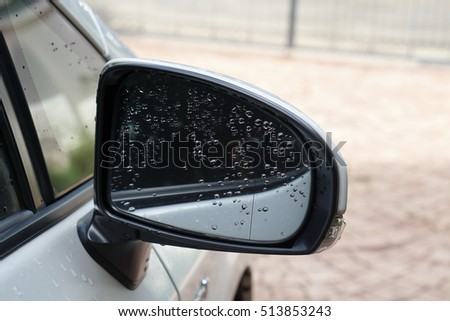 water drop on glass on car side mirror of white car