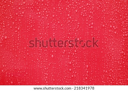 Water drop on red background. - stock photo