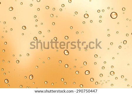 Water drop on sunset glass mirror background.