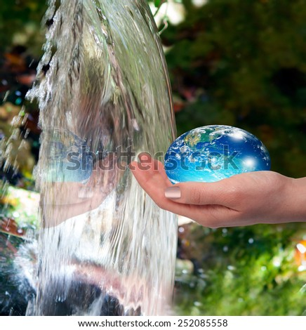 "Water drop shape in the hand ( drinking water crisis) ""Elements of this image furnished by NASA ""  - stock photo"