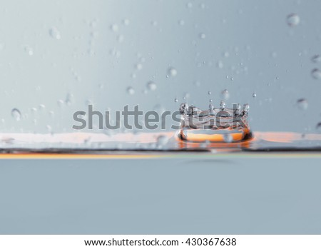Water drop splashing with waves - stock photo