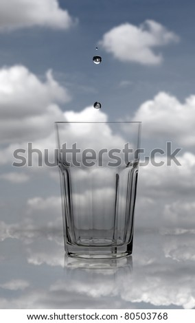 Water droplet dripping into an empty crystal glass against a cloudy blue sky. - stock photo