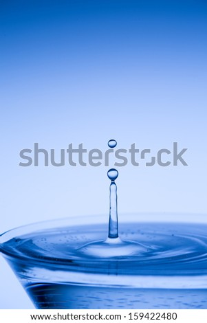 Water droplet suspended above a blue cocktail in a martini glass against a blue background with copyspace