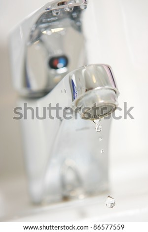 Water droplets at faucet - stock photo