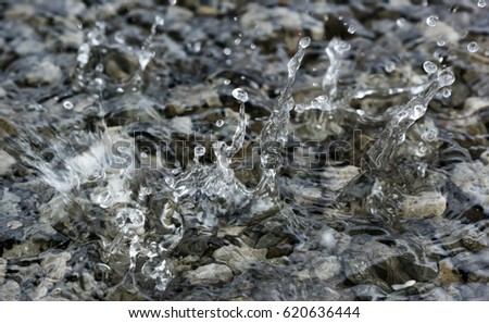 Water droplets falling into the small pool of water covering small stones creating intricate splash patterns