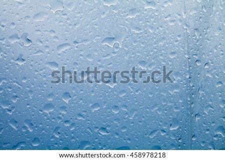 Water droplets from rain on glass, blue background - stock photo