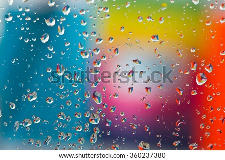 water droplets on a glass with a colourful background - stock photo