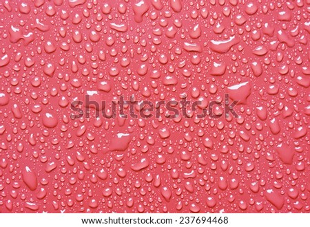 Water droplets on a red plastic sheet. - stock photo