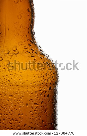 Water droplets on chilled transparent brown beer bottle