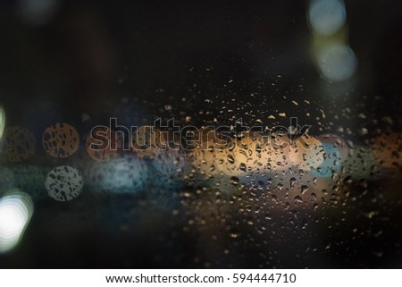 Water droplets on glass against the background of Boke. Artistic style - Defocused urban abstract texture background for your design, Defocused cityscape at night light background