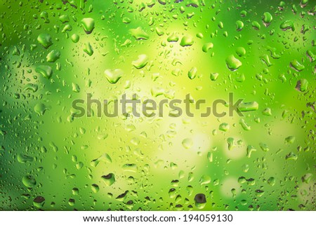 Water droplets on glass, bright green background - stock photo