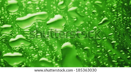 water droplets on glass in green - stock photo