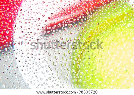 Water droplets on glass with background yellow and red colors - stock photo