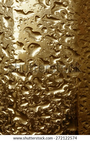 Water droplets on golden metal - a beautiful unusual texture - stock photo