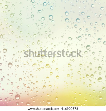 Water droplets on the glass with a colored background. Drops of rain on the window with color filter image. - stock photo