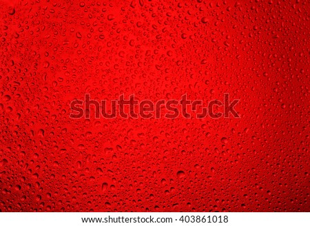 Water droplets on the glass with a red illumination - stock photo