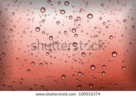 Water droplets on the red glass - stock photo