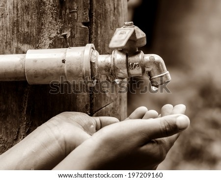Water dropped from the old tap on hand in dry season, rural area Thailand. - stock photo