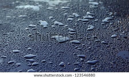 Water drops after heavy rain in the morning sunrise at metallic car paint - stock photo