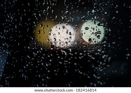 Water drops and lights on a car in the evening  - stock photo