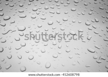 Water drops collect on top of metallic car surface as abstract background  - Rain drops - soft light tone - Black and White