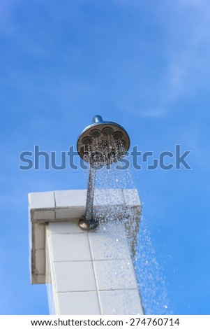 Water drops falling from a shower outside against blue sky - stock photo