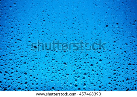 Water drops flow down on the glass in the rain, on a blue background - stock photo