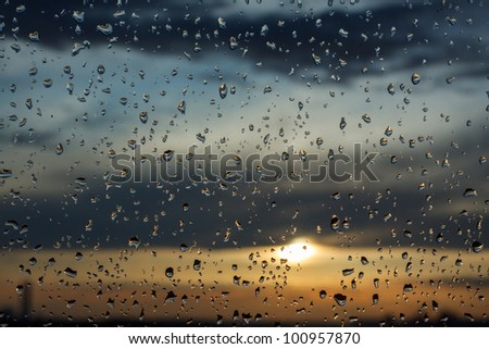 Water drops on a window glass after the rain. The sky with clouds and sun on background. - stock photo