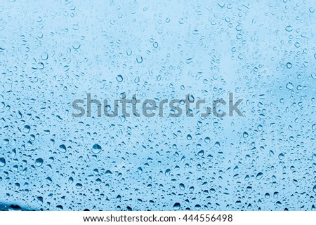 Water drops on blue background, raindrops over glass.