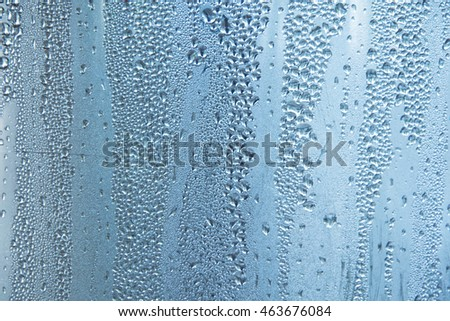 water drops on blue glass bokeh texture background with defocused lights