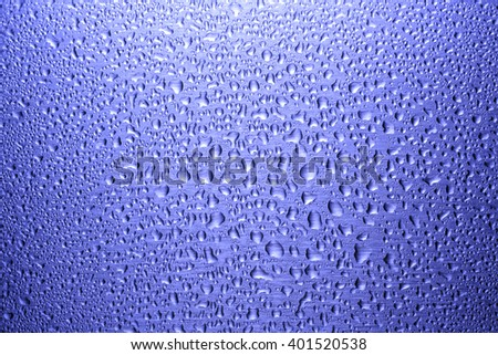 Water drops on blue glass surface - stock photo